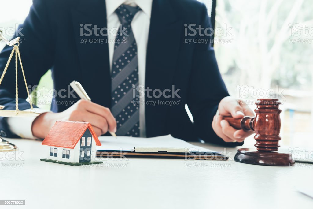 Real Estate Law concept. Gavel on sounding block in hand's Male judge at a courtroom, working for the insurance compensations. report the case on table in modern office. stock photo