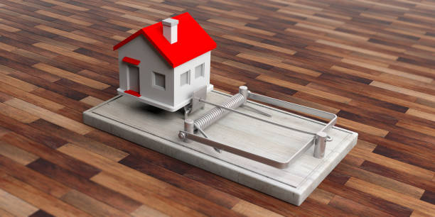 real estate loan trap. house on a mouse trap isolated on wooden floor background. 3d illustration - trap house stock pictures, royalty-free photos & images