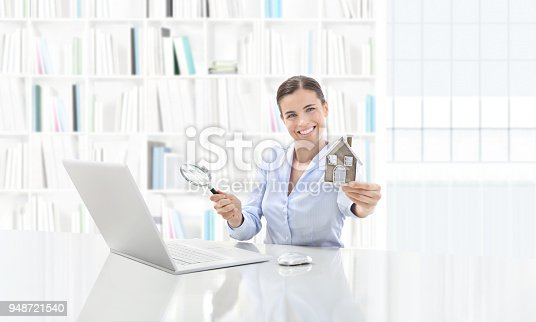 1023041738istockphoto real estate office, smiling woman agent working on computer with magnifying glass, search home concept 948721540