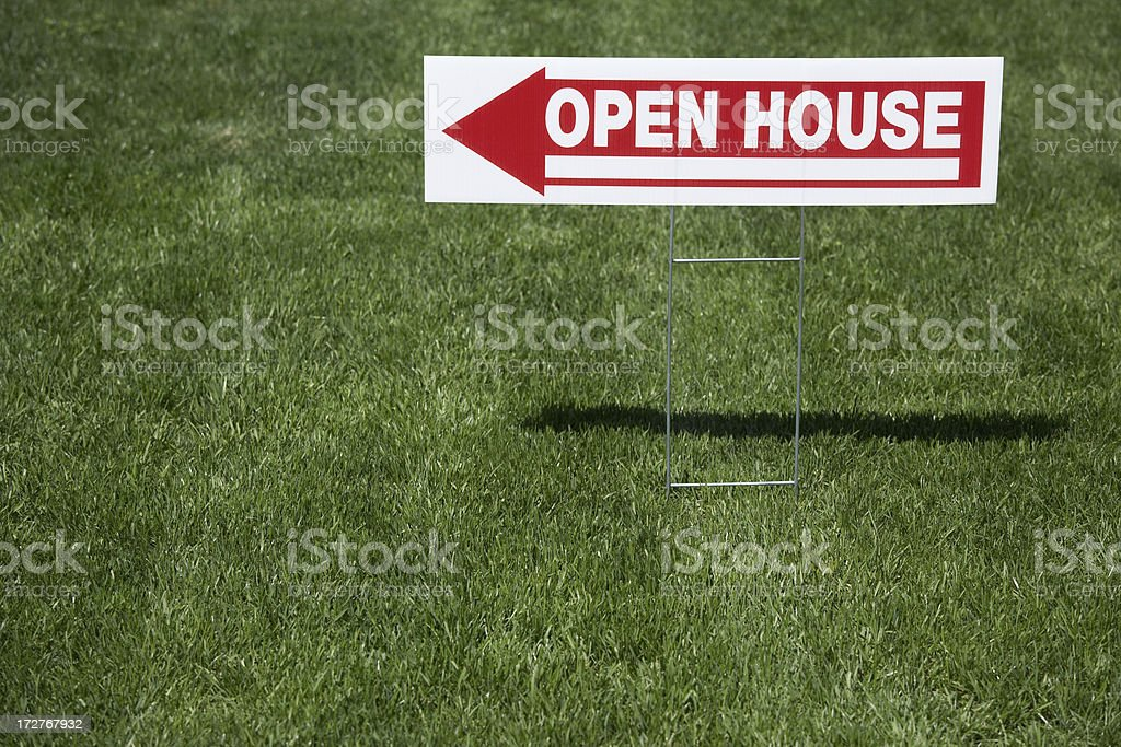 Real estate open house sign, red and white sign in grass. royalty-free stock photo