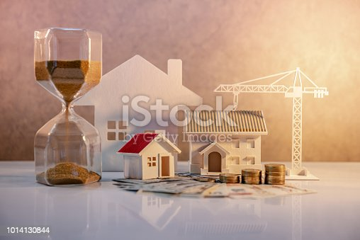 istock Real estate or property development. Construction business investment concept. Home mortgage loan rate. Coin stack on international banknotes with hourglasses, house and crane models on the table. 1014130844