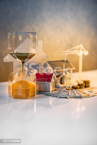 istock Real estate or property development. Construction business investment concept. Home mortgage loan rate. Coin stack on international banknotes with hourglasses, house and crane models on the table. 1014130898