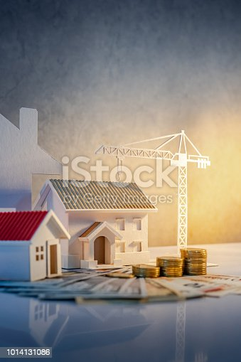 istock Real estate or property development. Construction business investment concept. Home mortgage loan rate. Coin stack on international banknotes with house and construction crane model on the table. 1014131086