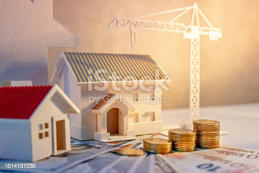 istock Real estate or property development. Construction business investment concept. Home mortgage loan rate. Coin stack on international banknotes with house and construction crane model on the table. 1014131230