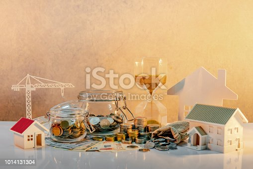 istock Real estate or property development. Construction business investment concept. Home mortgage loan rate. Coin stack and currency grass jar on banknotes with house and crane models, hourglass on table. 1014131304