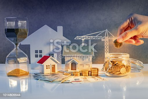 istock Real estate or property development. Construction business investment. Home mortgage loan rate. Hand putting coin in currency glass jar with Coin stack, banknotes, house and crane models on the table. 1014805544