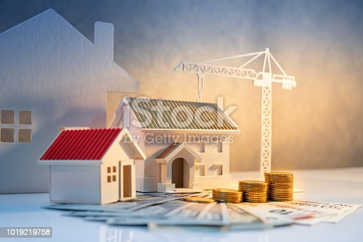 istock Real estate or property development. Construction business investment concept. Home mortgage loan rate. Coin stack on international banknotes with house and construction crane model on the table. 1019219758