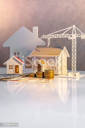 istock Real estate or property development. Construction business investment concept. Home mortgage loan rate. Coin stack on international banknotes with house and construction crane model on the table. 1022641312