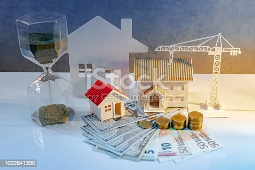 istock Real estate or property development. Construction business investment concept. Home mortgage loan rate. Coin stack on international banknotes with hourglasses, house and crane models on the table. 1022641330