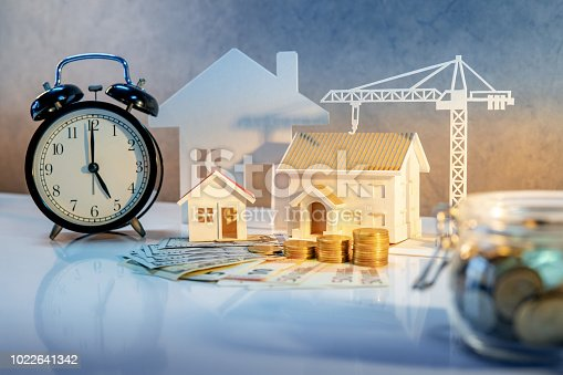 istock Real estate or property development. Construction business investment concept. Home mortgage loan rate. Coin stack on international banknotes with clock, house and crane models on the table. 1022641342