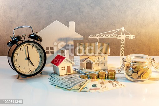 istock Real estate or property development. Construction business investment concept. Home mortgage loan rate. Coin stack on international banknotes with clock, house and crane models on the table. 1022641346