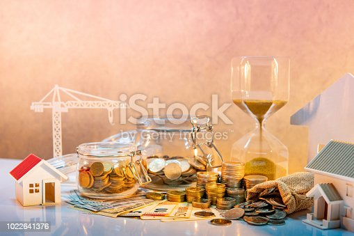 istock Real estate or property development. Construction business investment concept. Home mortgage loan rate. Coin stack on international banknotes with hourglasses, house and crane models on the table. 1022641376