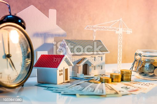 istock Real estate or property development. Construction business investment concept. Home mortgage loan rate. Coin stack on international banknotes with clock, house and crane models on the table. 1022641380