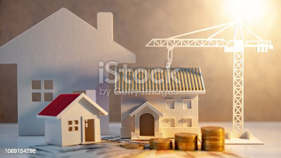 istock Real estate or property development. Construction business investment concept. Home mortgage loan rate. Coin stack on international banknotes with house and construction crane model on the table. 1069154298