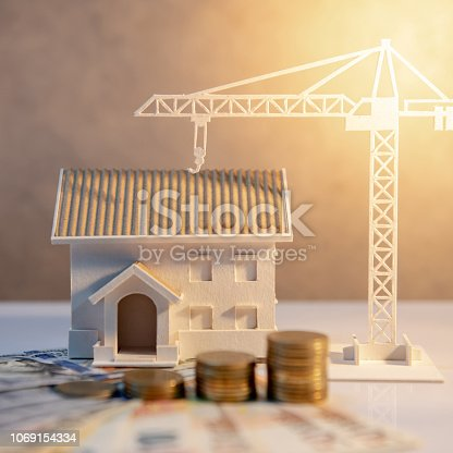istock Real estate or property development. Construction business investment concept. Home mortgage loan rate. Coin stack on international banknotes with house and construction crane model on the table. 1069154334