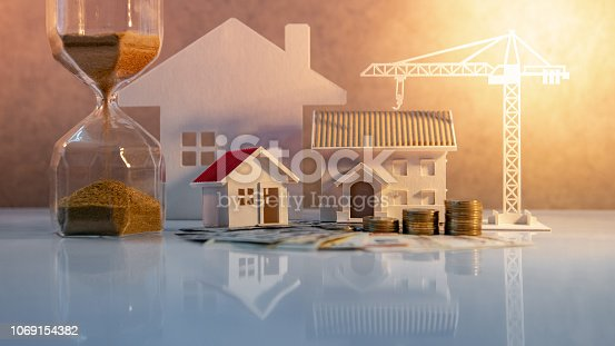 istock Real estate or property development. Construction business investment concept. Home mortgage loan rate. Coin stack on international banknotes with hourglasses, house and crane models on the table. 1069154382