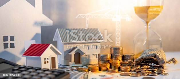 istock Real estate or property development. Construction business investment concept. Home mortgage loan rate. Coin stack on international banknotes with calculator, hourglasses, house and crane models on the table. 1069154396