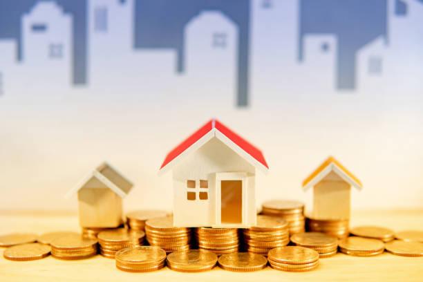 Immobilien-oder Immobilieninvestitionskonzept. Hypothekendarlehen für den Eigenheimhypothekendarlehen. Goldmünzen stapeln und Hausmodelle auf den Tisch mit weißem Skyline-Hintergrund. Geld sparen für den künftigen Ruhestand. – Foto