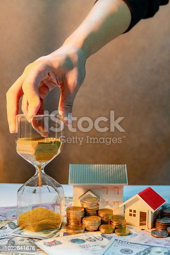 istock Real estate or property investment growing business. Home mortgage loan rate. Saving money for retirement concept. Male hand holding hourglass with house model and coin stack on banknotes on the table 1022641676