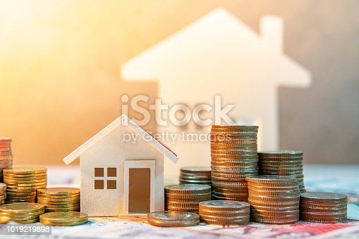 Real estate or property investment. Home mortgage loan rate. Saving money for retirement concept. Coin stack on international banknotes with house model on table. Business growth background