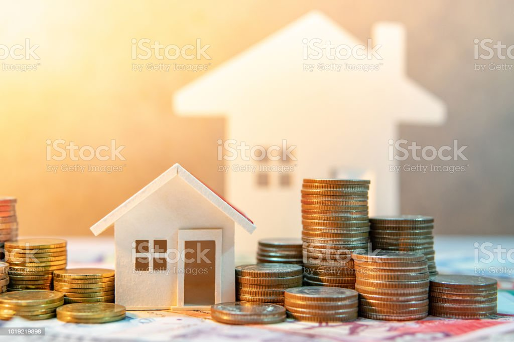 Real estate or property investment. Home mortgage loan rate. Saving money for retirement concept. Coin stack on international banknotes with house model on table. Business growth background stock photo