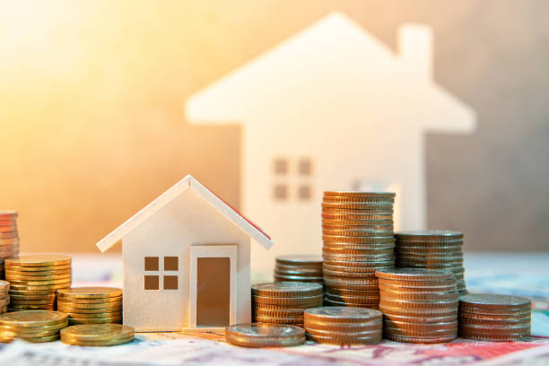 real estate or property investment. home mortgage loan rate. saving money for retirement concept. coin stack on international banknotes with house model on table. business growth background - {{asset.href}} foto e immagini stock