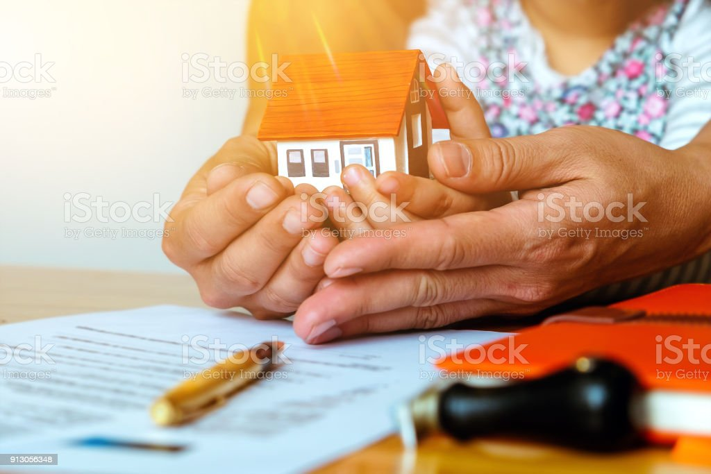 real estate purchase concept, Parent signing at contract document for buy house with his daughter. stock photo