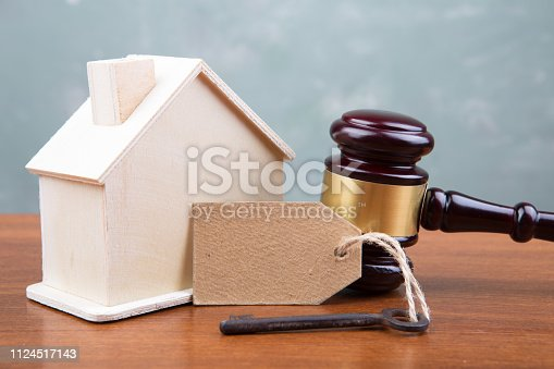 istock Real estate sale auction concept - gavel and house model on the wooden table 1124517143