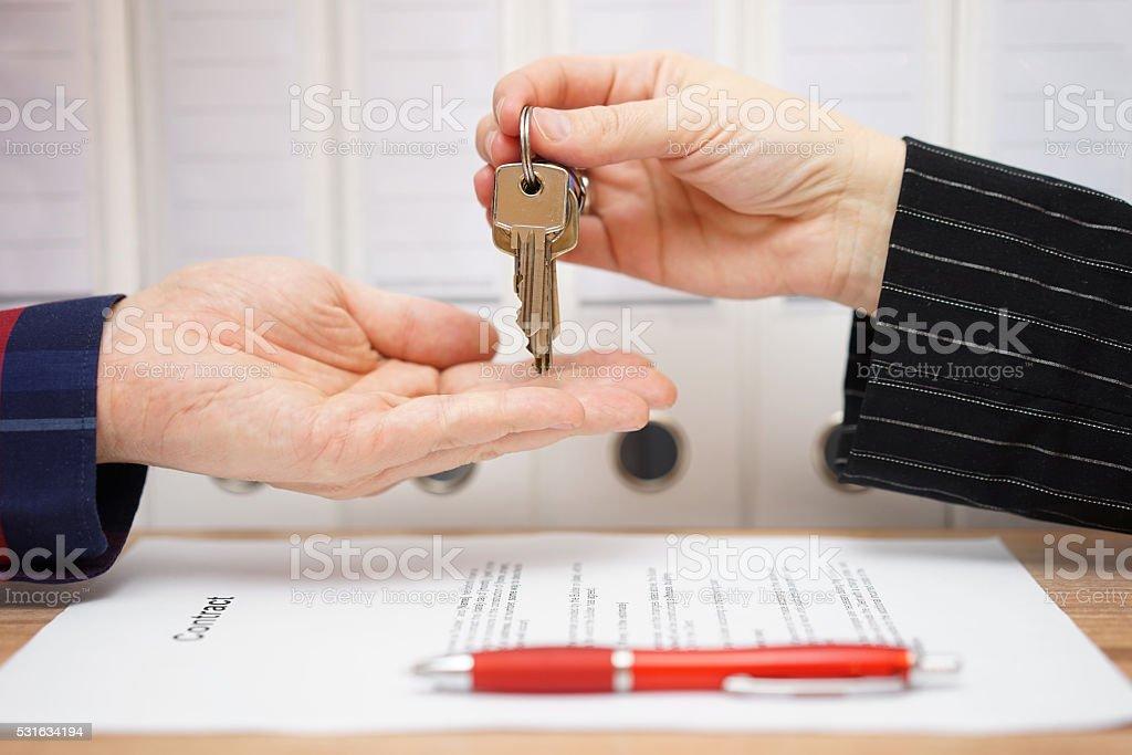 Immobilien der Verkäufer geben Autoschlüssel dem Käufer nach der Unterschrift – Foto