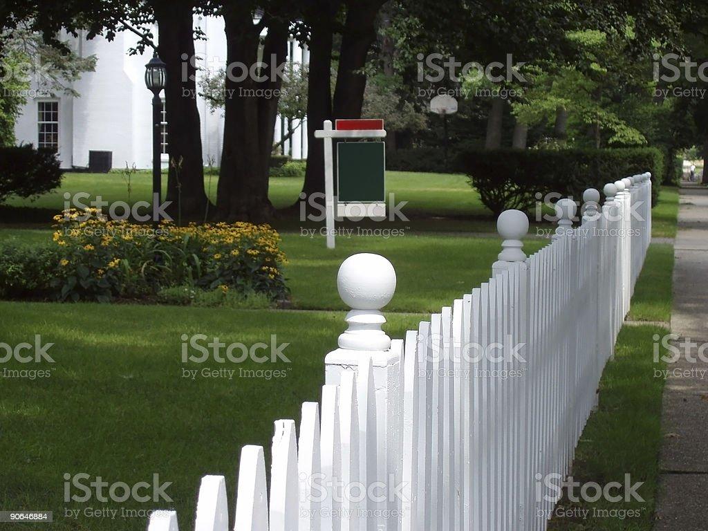 Immobilienzeichen Und Weißen Gartenzaun Stockfoto