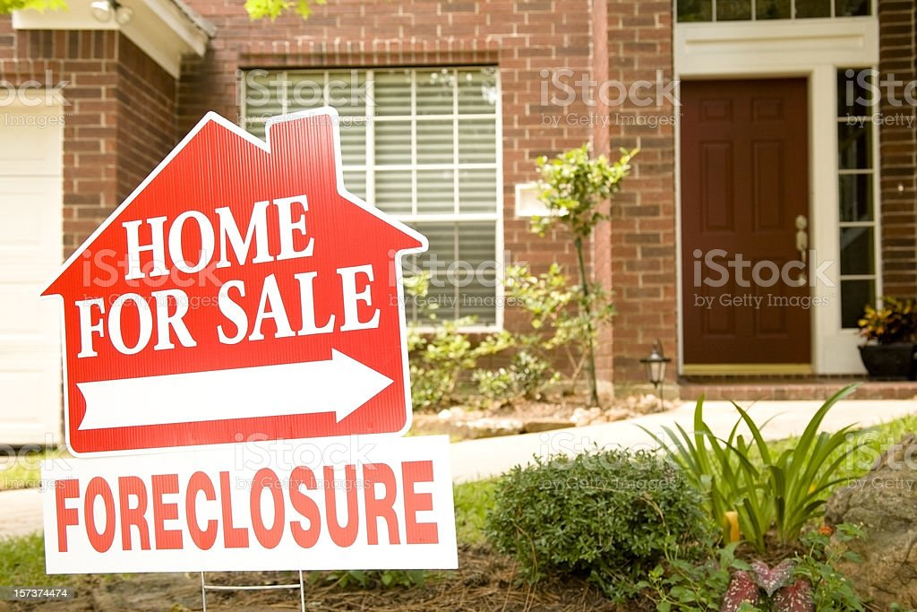 Real Estate Sign in yard of foreclosure house. For sale. stock photo