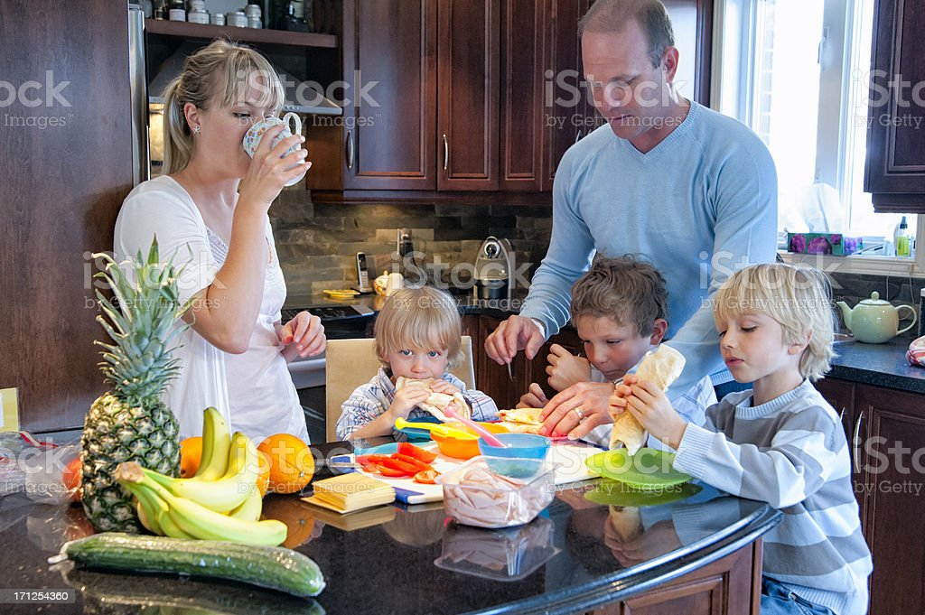 Real family of five eating healthy lunch on kitchen counter. royalty-free stock photo