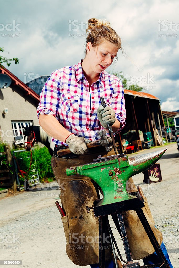 Real female farrier working at her anvil stock photo