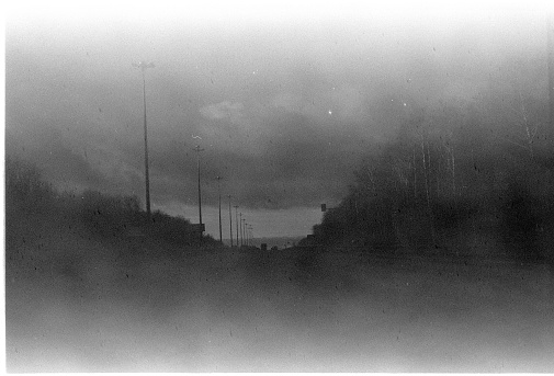 A real film, black and white 35 mm format spoiled photo with dust and scratches. 35mm photographic film with scratches, dust, dirt, out of focus image.