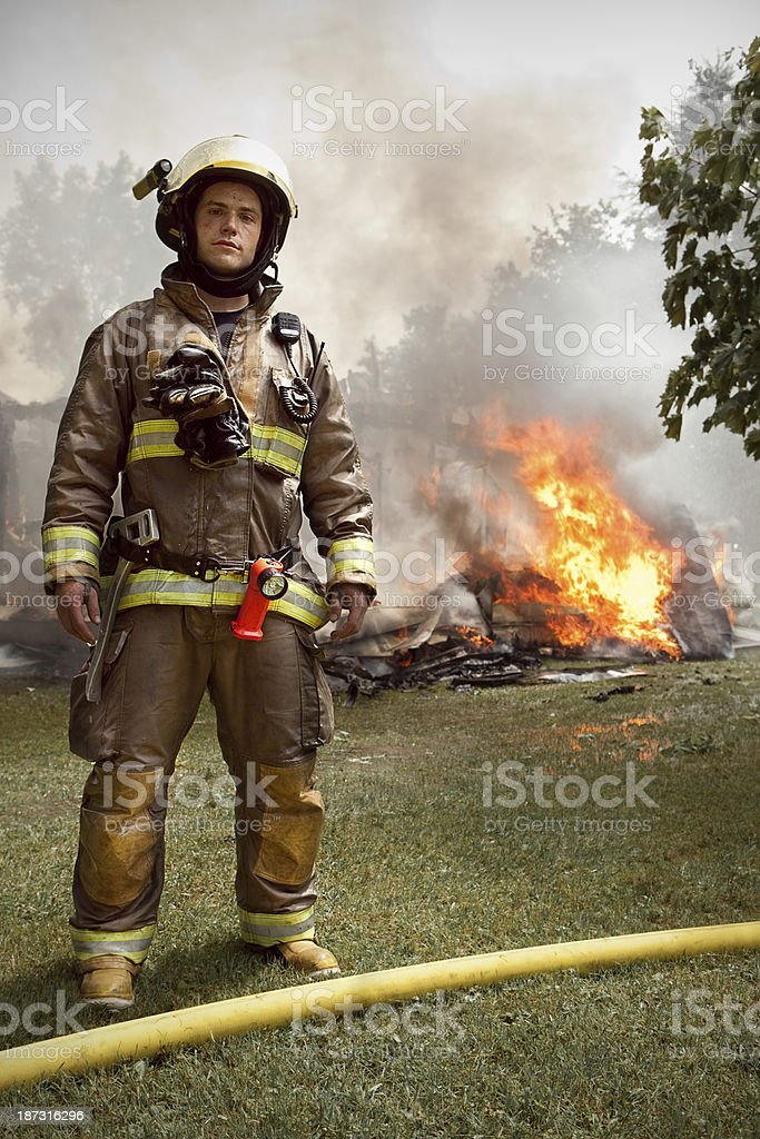 Real Firefighter with house on fire in background stock photo