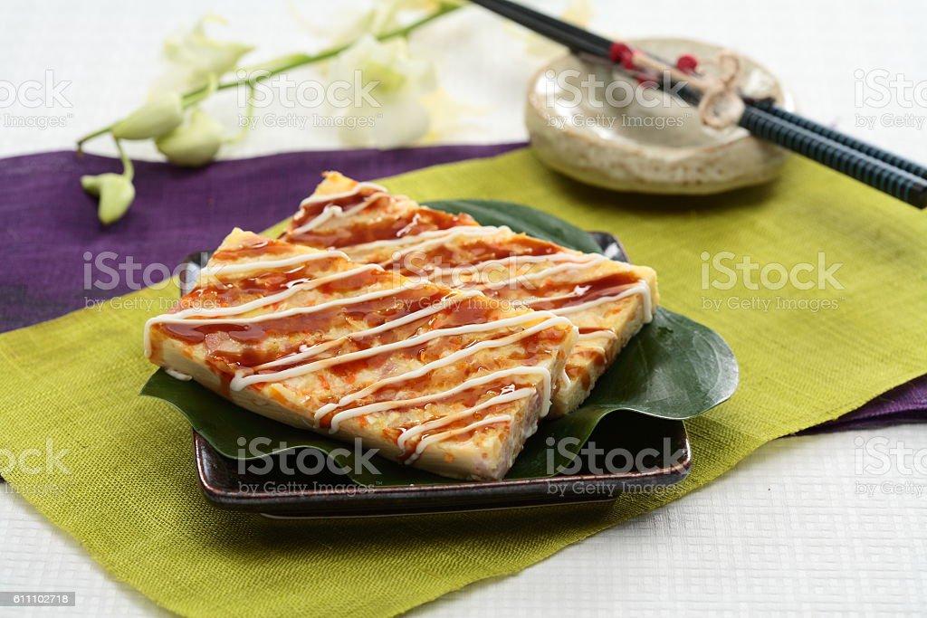 Real firmer okonomiyaki on green leaf and black plate in stock photo