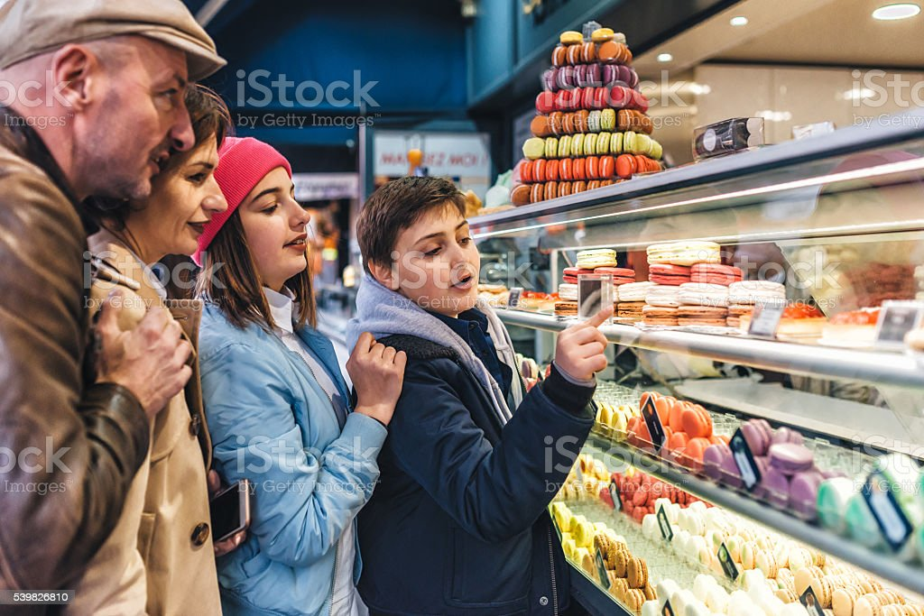 real french family at paris macarons stall stock photo