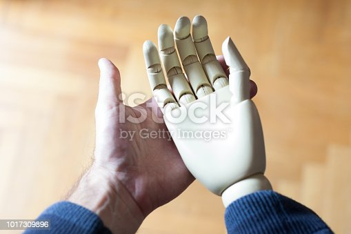 istock real hand holding prosthetic hand 1017309896