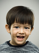 Close up portrait of little charming boy with sweet laugh on his face against gray background. Vertical shot of real kid smiling and happy in studio. Photography from a DSLR camera. Sharp focus on eyes.