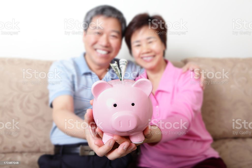 Real Happy senior couple with piggy bank royalty-free stock photo