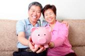 istock Real Happy senior couple with piggy bank 172467048