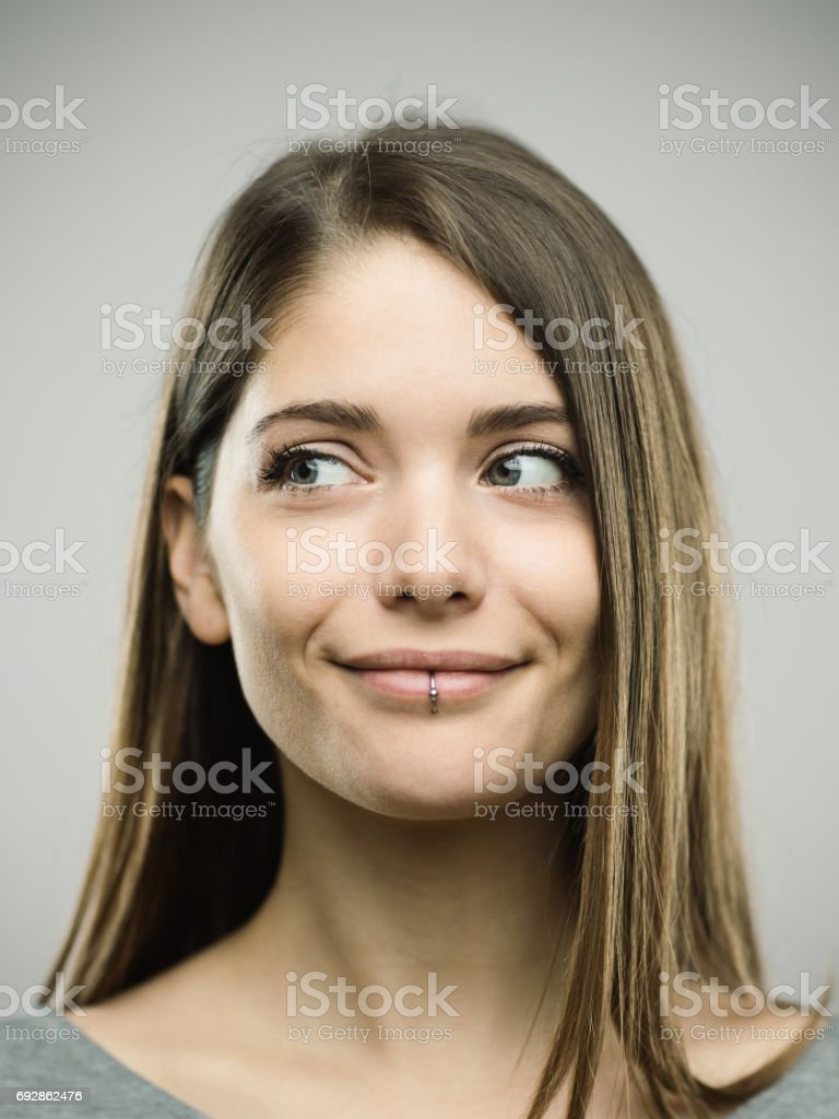 Real happy young woman studio portrait looking away stock photo