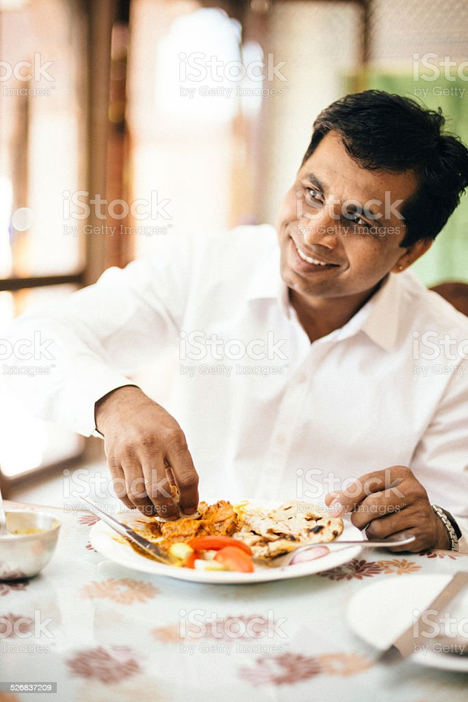 Real Indian man eating with hands in Indian Restaurant stock photo