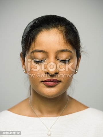 Close up portrait of indian young woman with blank expression resting against gray background. Vertical shot of real people with closed eyes in studio with long black hair. Photography from a DSLR camera. Sharp focus on eyes.