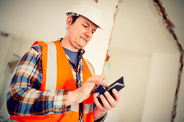 Real Italian worker using smart phone at working place stock photo