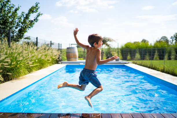 real life real people summer at home boy jumping in swimming pool stock photo