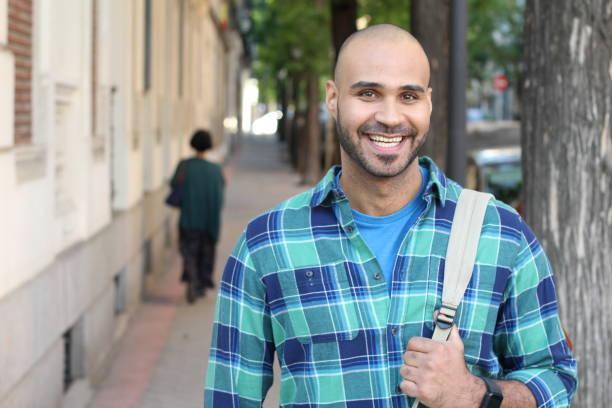 Homem étnico de vista real que sorri ao ar livre - foto de acervo