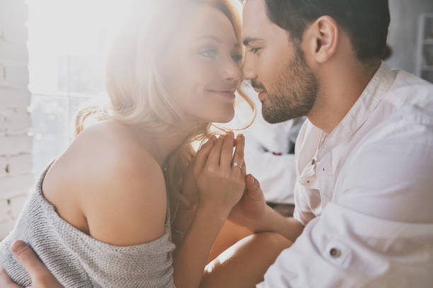Real love. Beautiful young couple bonding and smiling while sitting in the bedroom passion stock pictures, royalty-free photos & images