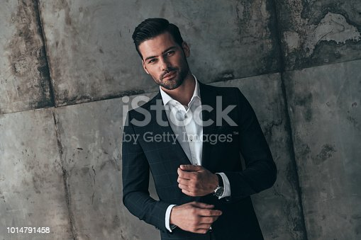Handsome young man in suit looking at camera and smiling while standing indoors