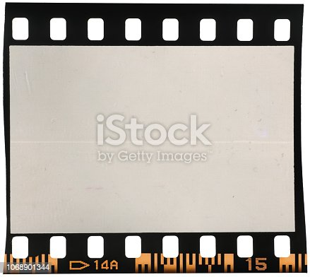 1129542015 istock photo Real macro photo of old and vintage looking 35mm film strip or dia frame on white 1068901344